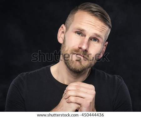 Young man asks for forgiveness on a dark background. - stock photo