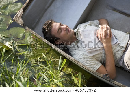 Young man asleep in a boat - stock photo