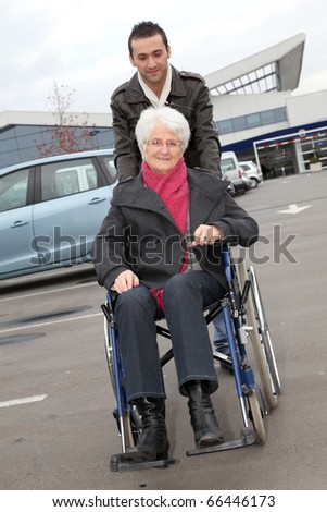 Young man assisting senior woman in wheelchair - stock photo