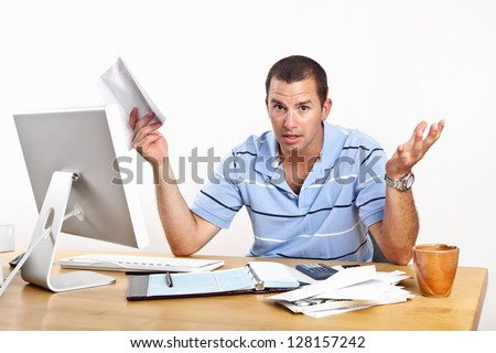 Young man at desk with computer and stacks of bills to be paid, with open checkbook. White background.