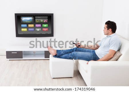 Young Man At Home Applying Setting Of Television Sitting On Couch - stock photo
