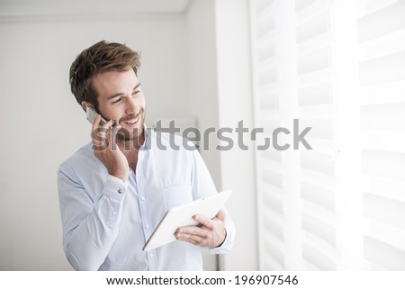 young man at phone using a digital tablet - stock photo