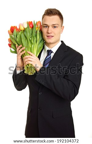 Young man at suit with tulips bouquet on their shoulders