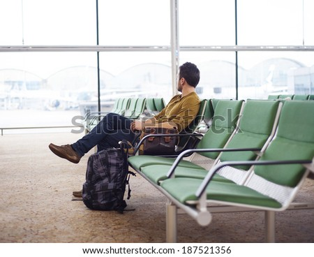 Young man at the airport waiting for his plane  - stock photo