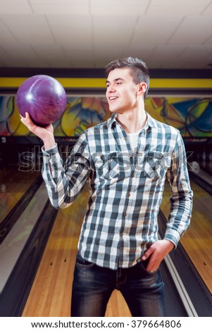 Young man at the bowling alley with the ball