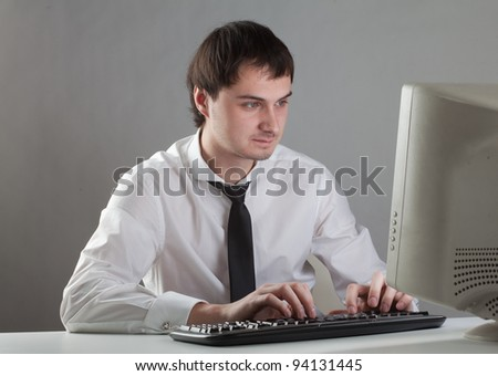 young man at the computer, staring at the monitor - stock photo