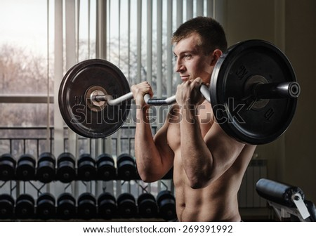 Young man at the gym lifting performs an exercise for biceps with a curved barbell. Toning, hard light.
