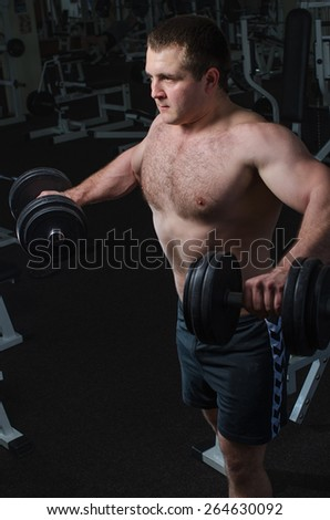 Young man at the gym to exercise the deltoid muscle of the shoulder, lifting dumbbells to the sides - stock photo