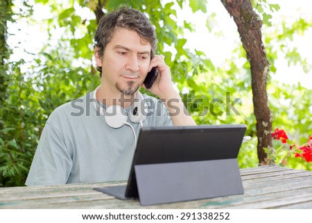 young man at the phone and tablet pc with headphones, outdoor - stock photo