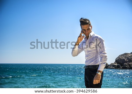 Young man at the seaside talking on cell phone while looking at the sea. Large copyspace - stock photo