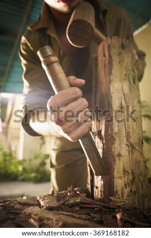 Young man at work learning craftsman profession, working with hammer and chisel. The artist carves a raw block of wood to make a wooden statue - stock photo
