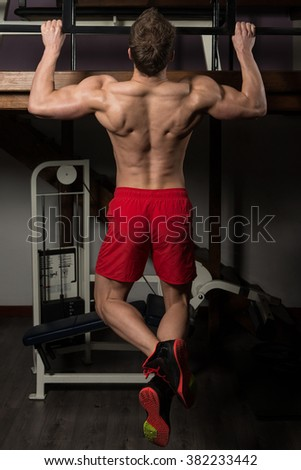 Young Man Athlete Doing Pull Ups - Chin-Ups In The Gym - stock photo