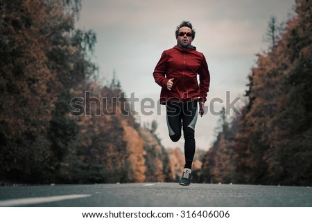 Young man athlete running hard on the asphalt road in the autumn forest