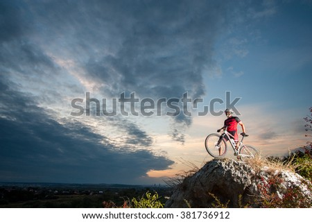 Young man athlete standing on top of a mountain with bicycle and enjoying view, with sky background. - stock photo