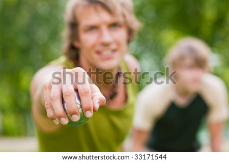 Young man attempting to throw the ball in a game of boule in a park - stock photo