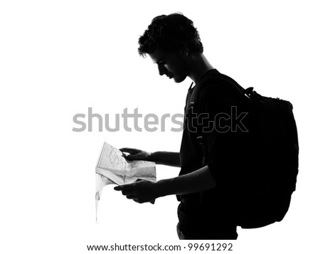 young man backpacker traveler looking at map silhouette in studio isolated on white background - stock photo