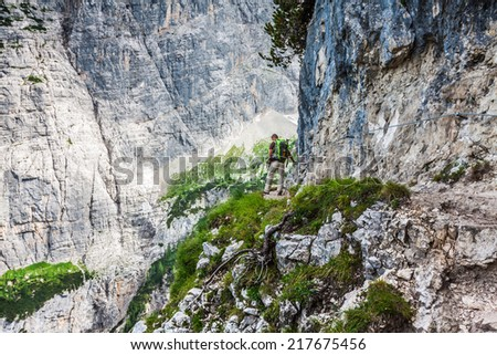 Young man backpacker walking on mountain trail Cinque Torri, Cortina d'Ampezzo, The Dolomites Mountains, Italy - stock photo