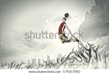 Young man basketball player with ball in hands jumping high - stock photo