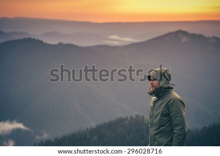 Young Man bearded standing alone outdoor with sunset mountains on background Travel Lifestyle and survival concept  - stock photo
