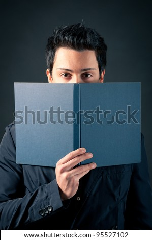 Young man behind a book against dark background. - stock photo