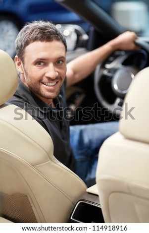 Young man behind the wheel - stock photo