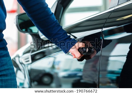 Young man beside a new car in car dealership, obviously he is buying the auto, or making a test drive - stock photo