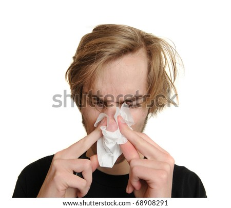 Young man blowing his nose because he is very ill and sick with a cold and fever. Isolated on white background. - stock photo