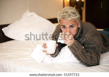 Young man blowing his nose in a tissue - stock photo