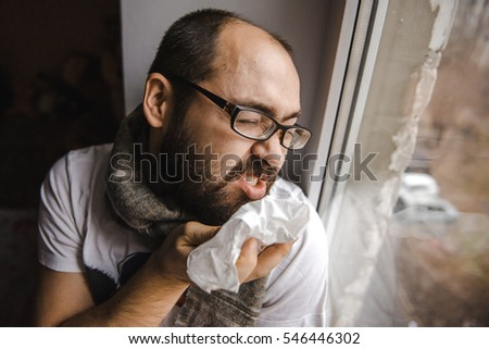 Young man blowing his nose while sitting at the window