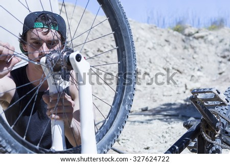 young man BMX biker fixing the wheel of his bike on a BMX session in the mountain - focus on the right eye - stock photo