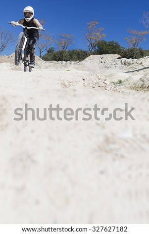 young man BMX biker riding with his bike on a BMX circuit in the mountain - focus on the head - stock photo
