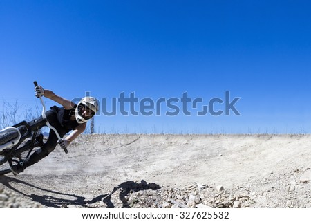 young man BMX cyclist riding with his bike on a BMX circuit in the mountain - focus on the head - stock photo
