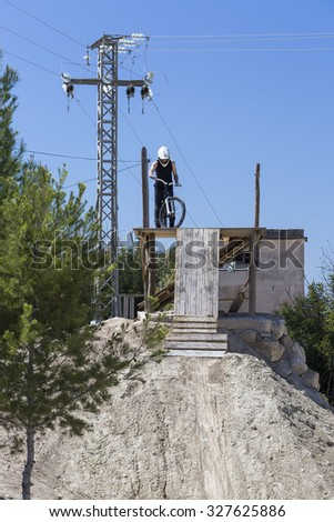 young man BMX rider is ready to jump on a wooden ramp on a BMX session in the mountain - focus on the face - stock photo