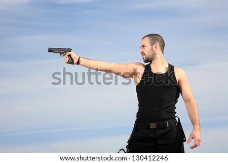 young man bodyguard with a gun outdoor - stock photo