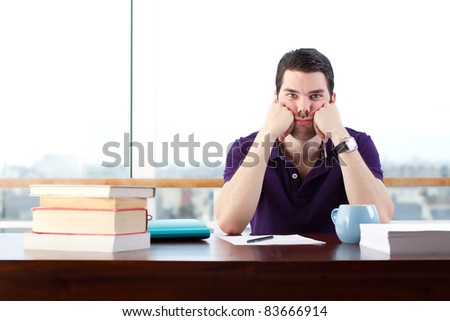 Young man bored of studying, looks a little sad - stock photo