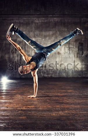 Young man break dancing on old wall background - stock photo