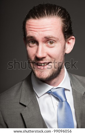 Young man brown long hair with expressive face wearing grey suit and blue tie. Isolated on grey background.