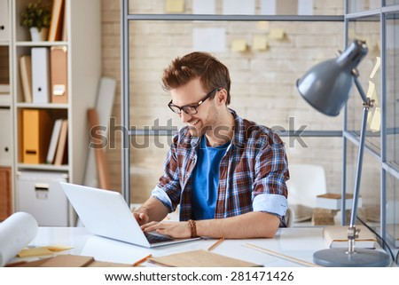 Young man browsing in laptop in office - stock photo