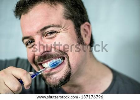 Young man brushing his teeth at home - stock photo