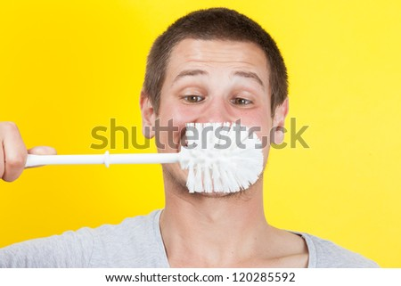 Young man brushing teeth with toilet brush - stock photo