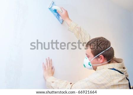 Young man builder polishing the wall. house environment theme - stock photo