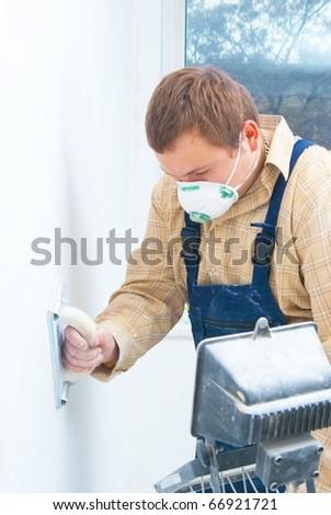 Young man builder polishing the wall. house renovation theme - stock photo