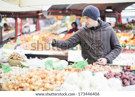 Young man buying fresh organic vegetables at farmer's market - stock photo