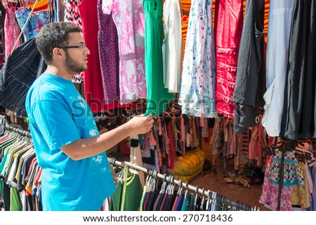 Young man buying in second hand store - stock photo