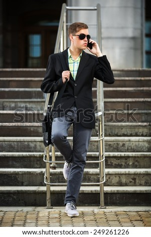 Young man calling on the mobile phone outdoor - stock photo