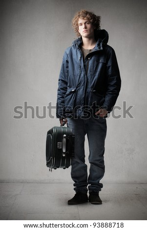 Young man carrying a trolley case - stock photo