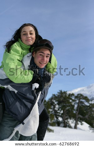 Young man carrying a young woman on his back - stock photo