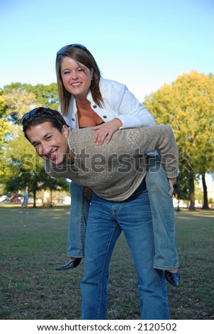 young man carrying attractive girl on his back