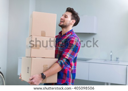 Young man carrying cardboard boxes  - stock photo