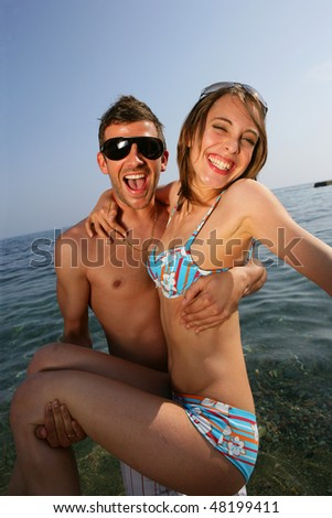 Young man carrying girlfriend in water - stock photo